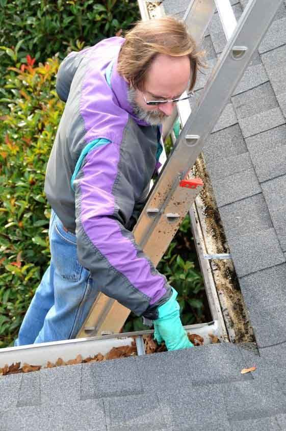 Cleaning gutters with gutter guards gutter helmet expert inspecting clogged residential gutter solutioingenieria Images